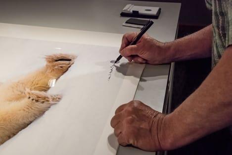 Thomas D. Mangelsen adding his thumb print and signature